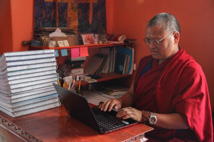 Menri Lopon Rinpoche working at his laptop profile
