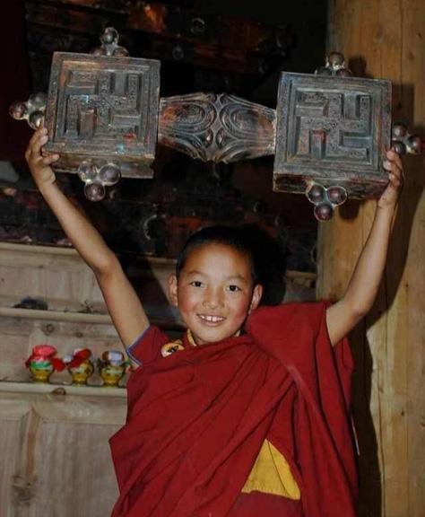 A young boy holds a wooden chakshing, symbol of Buddha Tonpa Shenrap Miwo