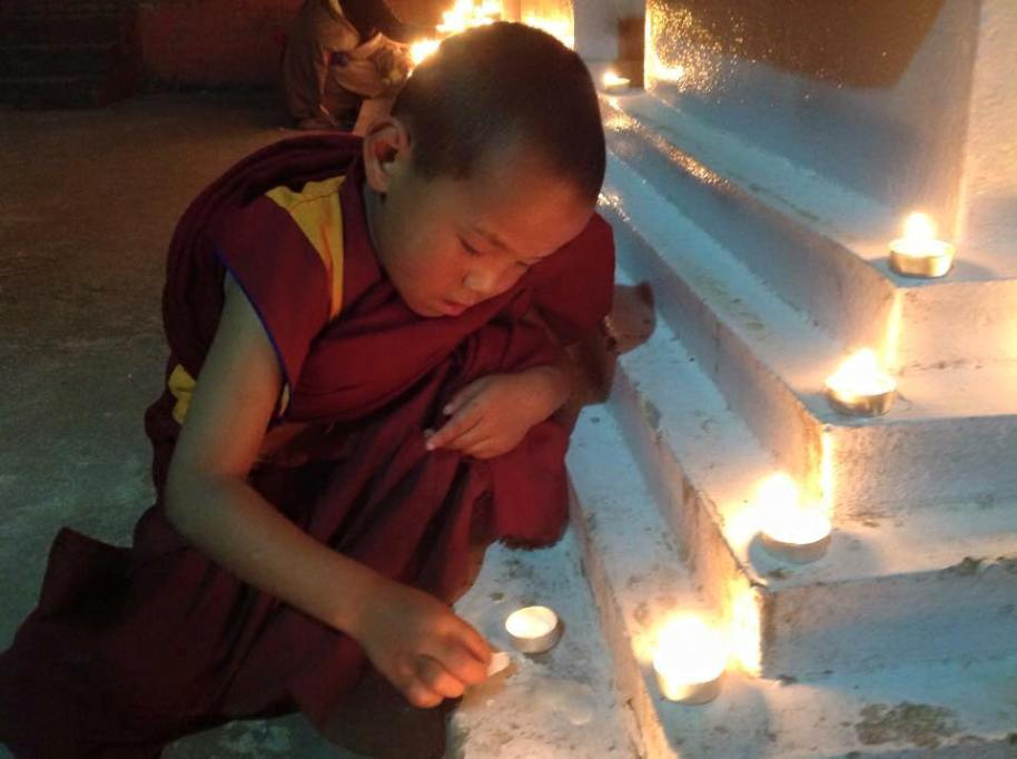 young monk lighting candle at stupa