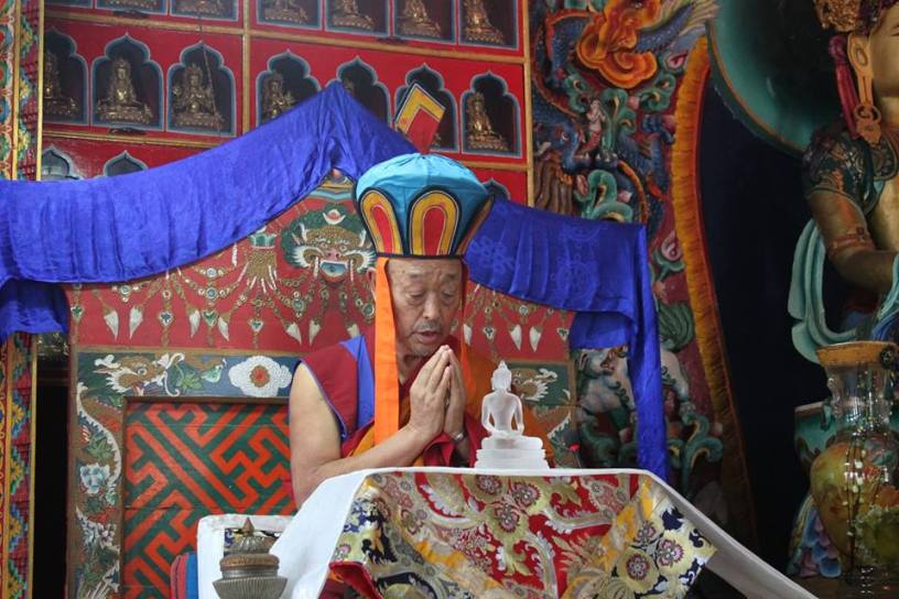 Menri Trizen praying with Kuntu Zangpo statue